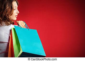 Eine Frau mit Einkaufstüten vor rotem Hintergrund