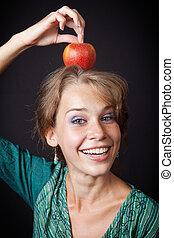 Eine Frau mit gesunden Zähnen und Apfel auf dem Kopf