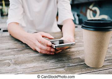 Eine Frau schreibt eine Nachricht, während sie mit einer Tasse Kaffee sitzt.