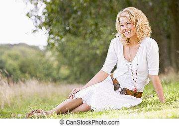 Eine Frau sitzt draußen und lächelt