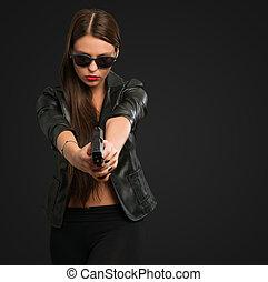 Eine Frau zielt mit einer Waffe