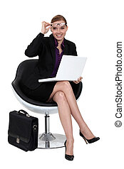 Eine Geschäftsfrau sitzt auf einem modernen Stuhl.