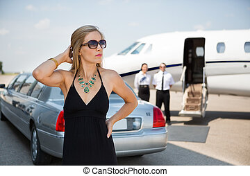 Eine gesunde Frau in elegantem Kleid am Terminal.