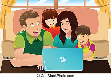 Eine glückliche Familie, die auf einen Laptop schaut