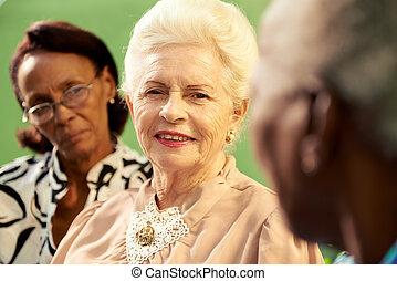 Eine Gruppe älterer schwarzer und weißer Frauen, die im Park reden