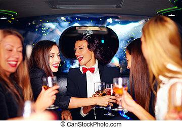 Eine Gruppe fröhlicher, eleganter Frauen, die ihre Brille in Limousine, Hühner-Party klinken.
