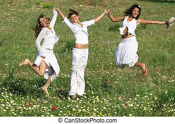 Eine Gruppe glücklicher junger Frauen springt im Sommer oder Frühling