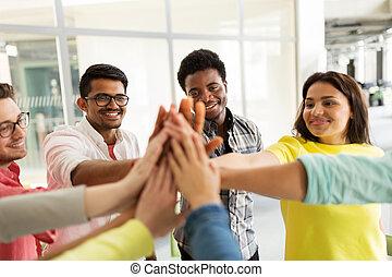 Eine Gruppe internationaler Studenten, die hohe fünf sind.