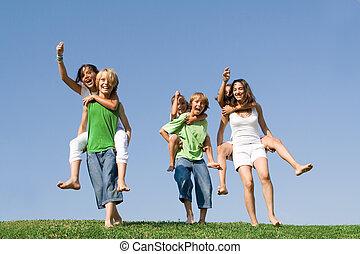 Eine Gruppe von Kindern im Ferienlager oder in der Schule, die ein Huckepackrennen veranstalten.