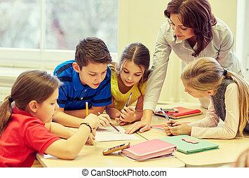 Eine Gruppe von Schülern, die im Klassenzimmer schreiben.