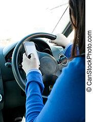 Eine junge Brünette, die ihr Handy beim Fahren benutzt