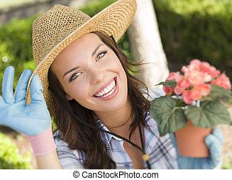 Eine junge erwachsene Frau, die einen Hut im Garten trägt