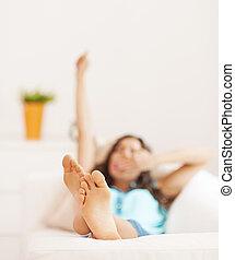 Eine junge Frau, die sich nach dem Schlafen erstreckt