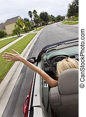 Eine junge Frau fährt ein Cabrio mit Hand in der Luft