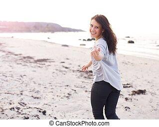 Eine junge Frau rennt und lädt Sie ein, näher zu kommen