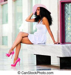 Eine junge schwarze Frau mit Kleid und Sonnenhut, afro-Haarstil