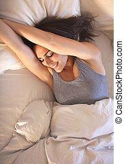 Eine lächelnde Frau auf dem Bett, die ihre Arme ausstreckt