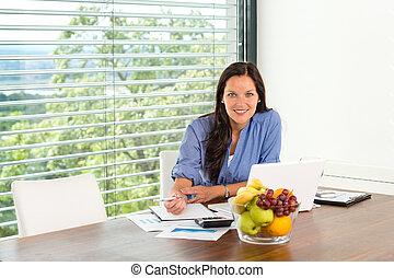 Eine lächelnde Frau, die an einem Laptop arbeitet.