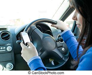 Eine schöne Brünette, die ihr Handy beim Fahren benutzt