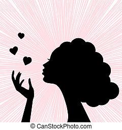 Eine schöne Frau steht vor Silhouette mit Herzküssen