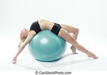Eine weiße Frau beim Fitnessballtraining.