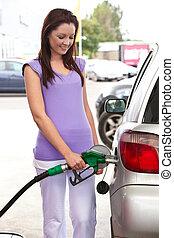Eine weiße Frau, die ihr Auto betankt
