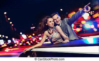 Elegantes Paar fährt nachts eine Limousine
