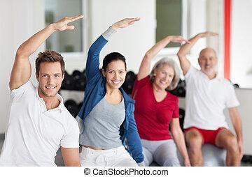 Enthusiastische Gruppe macht Aerobic in einem Fitnessstudio