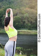Entspannte Frau, die frische Luft atmet und Arme hebt.