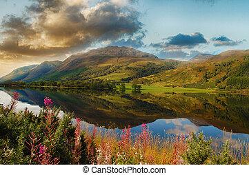 Epic landschaftlicher See in den scottish Highlands. Wunderschöne Landschaft von Schottland mit Bergen, Blumen und einem See mit Wasserspiegeln