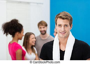 Er lächelt gutaussehender junger Mann im Fitnessstudio.