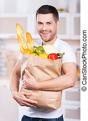 Er liebt gesundes Essen. Ein glücklicher junger Mann mit einem Einkaufsbeutel voller Lebensmittel während er in der Küche steht