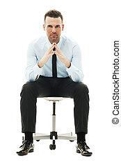 Ernster Geschäftsmann sitzt auf dem Stuhl