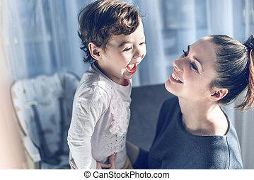 Erschöpfte Mutter, die ihr geliebtes Kind kuschelt.