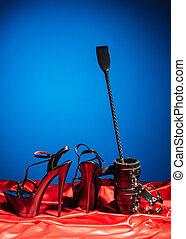 Erwachsene Sexspiele. Ein perverser Lebensstil. Schnürsenkel und ein Paar schwarzer Hochglanzschuhe auf der roten Leine. Bdsm-Outfit