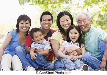 Erweiterte Familie sitzt draußen und lächelt