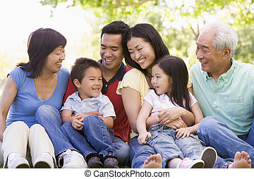 Extended Familie sitzen draußen lächelnd.