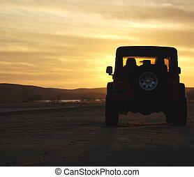 Fahrzeug in der Wildnis bei Sonnenuntergang