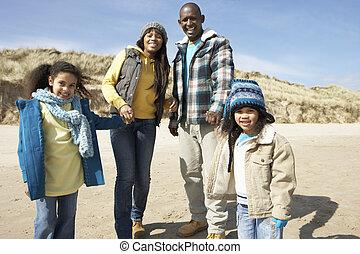 Familie läuft am Winterstrand