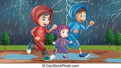 Familie läuft im Regen.