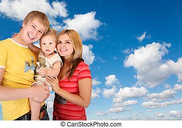 Familie mit Junge auf Weiß, fluffige Wolken im blauen Himmel kollabieren