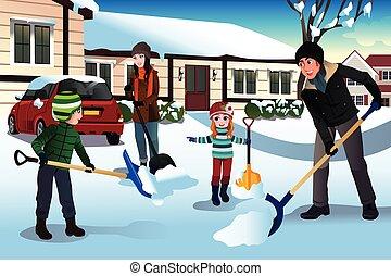 Familie schippt Schnee vor ihrem Haus.