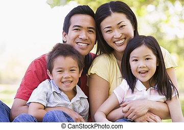 Familie sitzt draußen und lächelt.