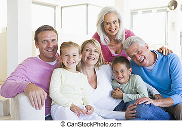 Familie sitzt drinnen und lächelt.