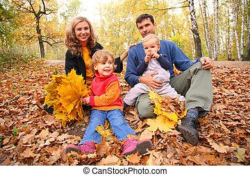 Familie von vier mit gelben Ahornblättern sitzt im Herbst in Holz.
