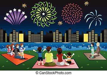 Familien sehen Feuerwerke in einem Park.