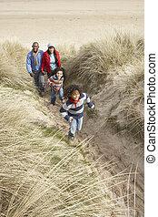 Familienspaziergang entlang der Dünen am Winterstrand.