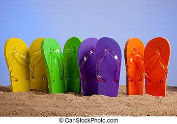 Farbige Flip-Flop-Sandles an einem sandigen Strand