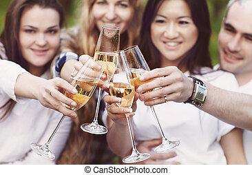 Feiern. Leute mit Champagnergläsern machen einen Toast draußen