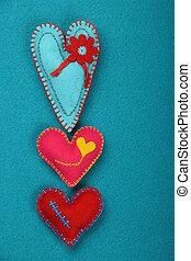Felt Handwerk und Kunst drei genähte Herzen auf blau.